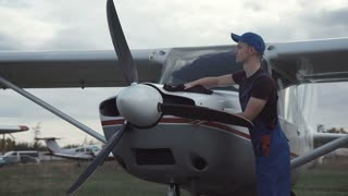 Young pilot or mechanic working on an aircraft wiping down the nose cowling on a small plane parked outdoors on an airfield