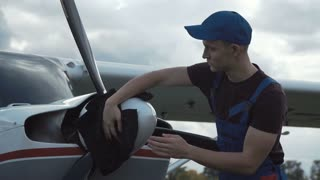 Young pilot or mechanic working on an aircraft wiping down the propeller on a small plane parked outdoors on an airfield
