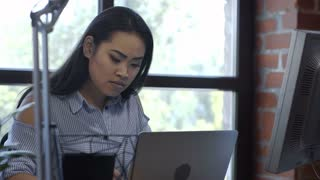 Young stylish Korean woman with long hair sitting at table in modern office and working with computer
