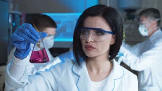 Young woman holding test tube and watching chemical reaction
