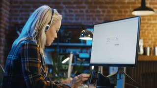 Young woman in headphones watching computer while working and surfing webpages