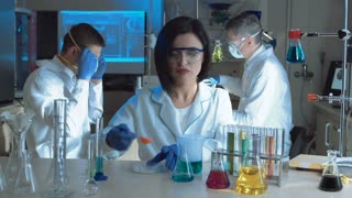 Young woman in special uniform holding test tube and watching chemical reaction