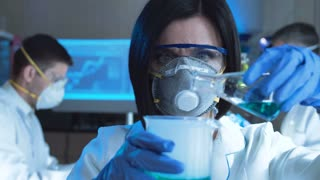 Young woman in special uniform holding test tube with blue liquid and watching chemical reaction