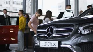 ZAPOROZHYE, UKRAINE - APRIL 3, 2018: View of expensive new car in auto salon with people and consultants walking around and having presentation. Movement stabilized 4k shot.
