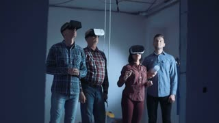 Zoom in movement shot of group of colleagues designers developers on glasses of virtual reality and watch this project in the 3D simulator then take off VR handshaking and looking on camera