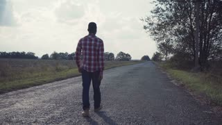 View of classy african american guy walking towards camera than away from it on countryside road