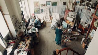 Wide view of a female artist wearing a smock standing in her studio painting a canvas on an easel surrounded by other covered canvasses and art supplies