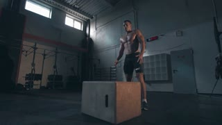 Wide view slowmotion single shirtless young man in dark shorts in motion doing jumping exercises in large crossfit gym hall