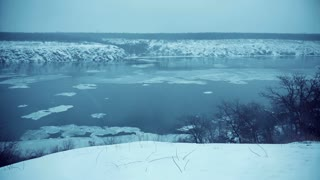 Winter snow weather, big blocks of ice flow on a current down the river between rocks, 4K wide shot