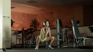 Woman doing sport exercise squats and jumps