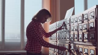 Woman searching the book in the catalog stack in library