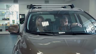 Young adult man and woman inside shiny new gray automobile with reflections of light in front window. The seller tells the couple about the new car in showroom