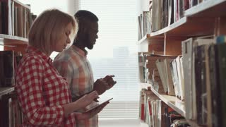 Young african man wearing eyeglasses and woman standing between stacks in library and reading the book