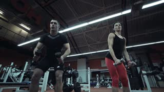 Young athletic woman training in gym with coach and lifting weights. Wide shot