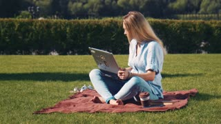 Young attractive blond barefoot woman using a laptop outdoors sitting on a rug on the grass in a garden in the summer sun