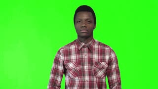 Young black male in plaid shirt standing and lost in thought on green chromakey background. 4K