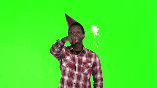 Young black man celebrating with a sparkler in his hand and wearing a party hat, upper body on bright green with copy space