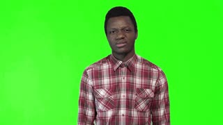 Young black man in plaid shirt standing and making displeased face on green chromakey background. 4K