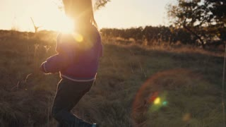Young blonde girl running at sunset in countryside. Autumn weather