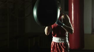 Young boxer hitting punching bag in gym
