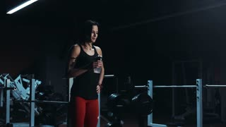 Young brunette female in sport outfit drinking water in gym and training
