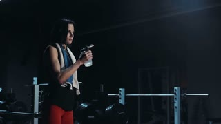 Young brunette female in sport outfit drinking water in gym