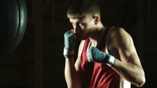 Young caucasian Boxer training with a punching bag in gym