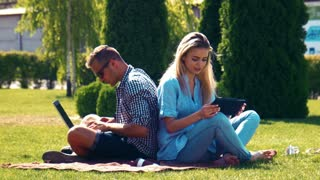 Young couple enjoying the summer sunshine sitting back to back on a rug on a lawn using a laptop and tablet computer