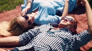 Young couple having fun relaxing together in the sun lying on their backs on a rug on the grass in their sunglasses chatting and smiling