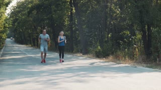 Young fit couple running side by side along a forest road in a healthy active outdoor lifestyle concept coming towards the camera with copy space