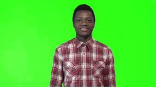 Young funny black man in plaid shirt smiling and giving thumbs-up on green chromakey background. 4K shot