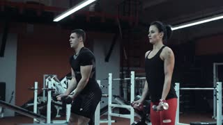 Young man and woman lifting weights in a gym as they train together toning and strengthening their muscles , low angle with raised dumbbells