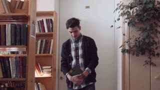 Young man student checked shirt walking through library while reading book, following camera. Low angle shot