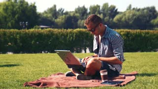 Young man using his laptop outdoors on the lawn sitting cross-legged on a rug on the grass with a takeaway coffee