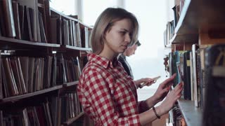 Young pretty girl student with blonde hair looking for right book in library, flipping pages standing at bookshelves