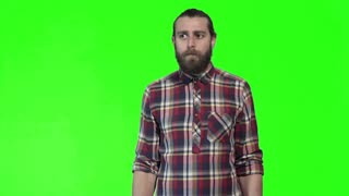 Young puzzled bearded man in plaid shirt posing and gesturing on green chromakey background. He is condemns