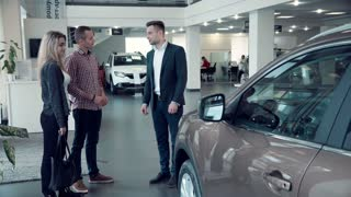 Young Salesman Delivering Sales Pitch to Couple Buying New Vehicle inside Car Dealership While Standing in front of Shiny New Model of car or electrocar