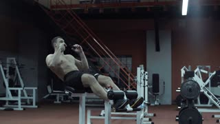 Young topless strong muscular man doing press exercise on bench while workout in modern gym