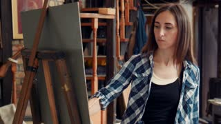 Young woman artist standing painting a canvas in a studio with her head tilted to the side and an absorbed expression