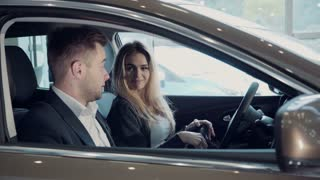 Young woman going for a test drive with the salesman in a new car as she makes a selection for her purchase, or she to pass virtual exam for driver license using virtual reality glasses