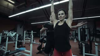 Young woman working out in a gym with a personal trainer lifting weights raising a pair of dumbbells above her shoulders, low angle view in a fitness and healthy lifestyle concept