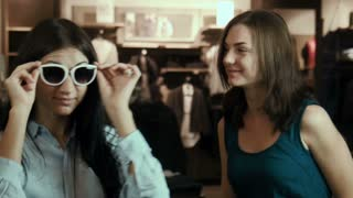 Two girls tries on sunglasses.