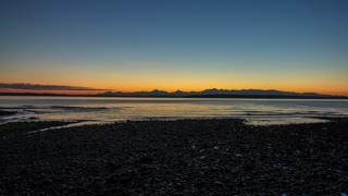 Time lapse of a sunset over the olympic mountains in Seattle Washington.