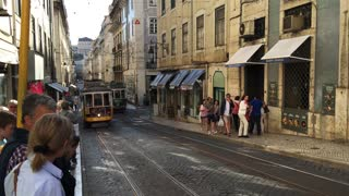 A yellow tram and a go car downtown Lisbon Portugal