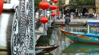 Boat enter the Cau An Hoi bridge with red lanterns in Hoi An Vietnam