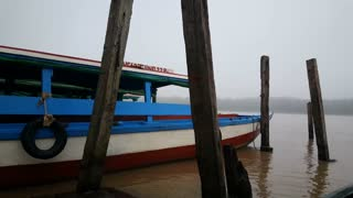 Boat leaving harbor on a misty river in Suriname