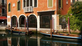 Boats and house reflection in a Canal in Venice Italy