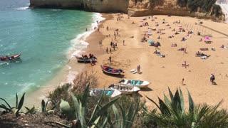 Boats and tourists at Praia de Carvoeiro in Algarve Portugal