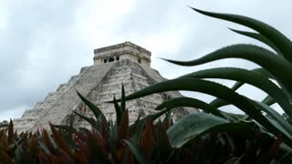 Chich_n Itz� Mayan ruin in Yucat�n Mexico behind a plant