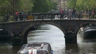 Close up Canal boat passing by a bridge in Amsterdam